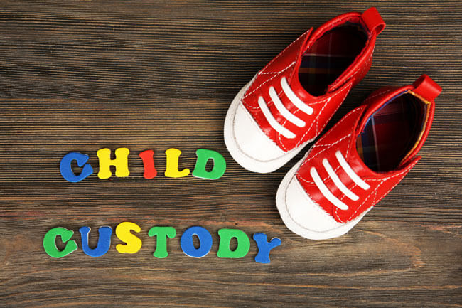 Children shoes with blocks spelling out child custody, an area of family law handled by the Edmonton law firm, Sharek & Co, which has divorce lawyers for legal matters such as separation, child custody, child support, spousal support, property division, emergency protection orders and restraining orders.
